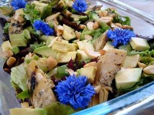 salatblade, grillede artiskokker, avokado, cashewnødder, kornblomster